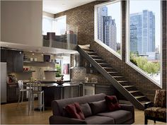 This loft is amazing! I really love how the windows angle up the staircase with the brick wall accent. Fantastic!
