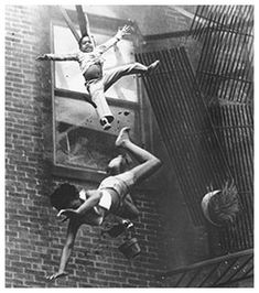 Fire Escape Collapse  On July 22, 1975 in Boston, a 19-year-old and her 2-year-old goddaughter were trapped in a burning building. A firefighter shielded them from the flames as a fire ladder inched closer. Then the fire escape collapsed. Although the woman died from her injuries, the infant survived. Fire Escape Collapse circulated around the world.  Photograph by Stanley Forman.  the savage fragility of being human.