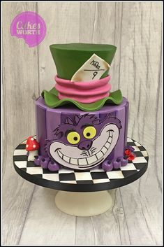 Alice in wonderland cake with mad hatters hat, cat and chequerboard details.