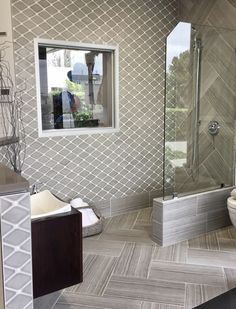 This modern walk-in shower is done in a stacked stone tile. It is bordered by their rock tile, which is also seen on the shower floor. #wetroom #framelessglassdoor #floatingvanity #glassshower #tileshower #showerideas #dreamshower #cheveronfloor #customshower #customtile