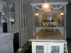 Architectural artifacts frame cook top with glass tile and terracotta floral plaques. Contemporary white cabinets, cement island top provide contrast. Lakeview Interiors