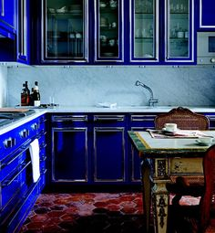 The secret to decorating the French way - the kitchen combines bold cabinetry in cobalt blue against terra-cotta-colored tiles and classic French antiques