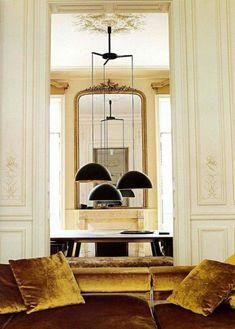 miroir doré, coussins en couleur ocre, lampes noires pendantes et grand miroir baroque