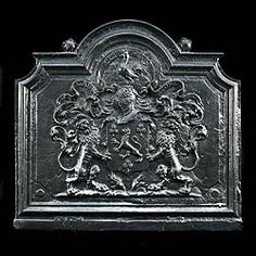A large burnished cast-iron fireback centred with an armorial shield flanked by scrolls and surmounted by a crowned cockerel. An exact replica of the sold 18th century French original.