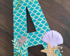 16in oversized freestanding letter photo prop. The perfect addition to you little ones birthday celebration or photo shoot! Made of a light weight paper mâché material, each letter is hand painted and embellished. Design is as pictured on front and painted solid on the back side to create a great view 360 degrees around! In keeping with the mermaid theme, textured starfish and seashells along with 3d wired pearls embellish the front side. Letter P and letter F do not stand up on their own.