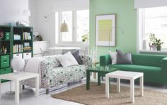 A bright living room with two two-seat sofas, one with a green cover and one with a fun pattern in green, pink and white. Combined with small side tables in green and white.