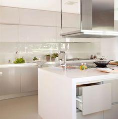 Cocina en blanco con isla central y antepecho de cristal
