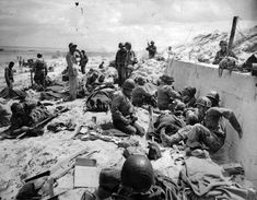 American soldiers lie on stretchers and sit propped against a sea wall awaiting transportation back to England for treatment after being wounded in the Normandy invasion, northern France, June 1944 during World War II. (AP Photo/Peter J. D Day Normandy, Normandy Beach, Normandy France, 4th Infantry Division, Mind Blowing Images, D Day Invasion, Normandy Invasion, D Day Landings, Red Beach