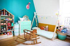 du bleu canard et de l'ocre jaune pour réveiller une chambre d'enfants, tout en douceur. Une jolie maison en bois pour ranger les jouets, un lit tipi Montessori, un cheval à bascule vintage , et Popi pour surveiller tout ce petit monde !
