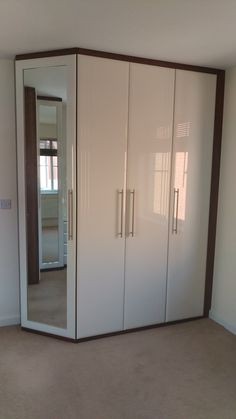 Fitted wardrobe with angled end door and recessed mirror with Dark Walnut carcass and high gloss ivory fronts. www.harmonymadetomeasure.co.uk