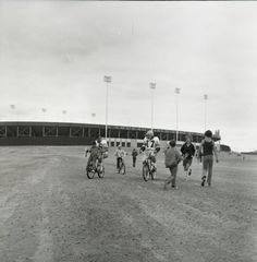 Here is an image displayed in our exhibit:  Green Bay Packers quarterbacks, Jerry Tagge (#17) and Scott Hunter (#16), ride bicycles loaned to them by young fans from Lambeau Field to their practice field during training camp. One player rides with a child on the handlebars while others jog or walk along. Lambeau Field is visible in the background.