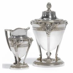 A Fabergé silver covered sugar bowl and cream jug, workmaster Alexander Väkevä (Wäkeva), St Petersburg, 1904-1908, in neoclassical taste, the urn-form bodies cast with winged lion's heads above tripod supports, chased leaf and berry boders, the circular bases centred with rosettes, the sugar bowl with fir cone finial, gilt interiors.