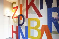 """The collaboration of Trend with Julia Bornefeld continues with the construction of a housing complex in Leipzig, considered the city of the German Book. In the historical building of the ex """"VEB Interdruck"""", Trend realizes the artwork of Julia Bornefeld representing aphorisms and words of german poets and writers. Colorful mosaic letters dress the decorate the walls, in a composition that combines art and literature."""