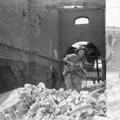 Men of the 2nd York and Lancaster Regiment searching the ruins of a railway station for Japanese snipers, during the advance of 14th Army to Rangoon along the railway corridor, 13 April 1945.