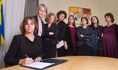 Isabella Lovin signs bill surrounded by women colleagues, apparently a reference photos of Trump signing bills surrounded by men