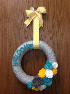 Welcome to our classroom yarn wreath! I used a dollar store pool noodle as the wreath form, wrapped it in light gray yarn, made felt flowers, painted small wooden letters, and added a ribbon to hang.