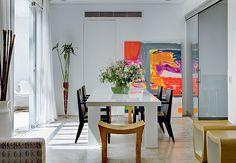 Aberta para o estar e integrado à cozinha por portas de correr de vidro, a sala de jantar tem mesa de laca branca e, para quebrar a monotonia, cadeiras pretas. Projeto de Simone Mantovani  Edu Castello / Casa e Jardim