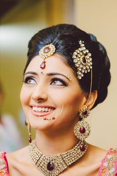 Love the smile on this gorgeous bride - and the jewels are pretty amazing too! Stunning stone and meenakari jewels, complete with choker, maang tikka, earrings, jhoomer and traditional bindis along her eyebrows - Indian bride - Indian wedding jewellery - wedding accessories - Indian bridal make up #thecrimsonbride