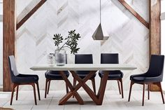 Enjoy the bold and modern design of the Moderna Dining Table by Insato Furniture in your home. This dining table features a walnut veneer base with a warm finish and geometric design that is the epitome of conceptual design. The series of intersecting bars create a unique base to support the table top securely and with style.