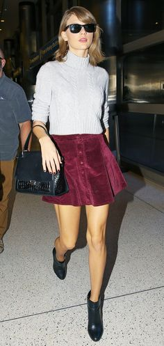 Taylor Swift wears a gray turtleneck with a red velvet skirt and black leather booties.