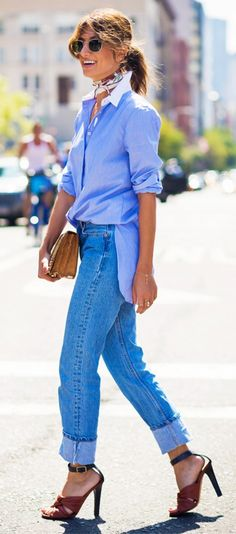 A menswear-inspired button-down shirt is paired with cuffed jeans, a neutral clutch, neckerchief, and sandals