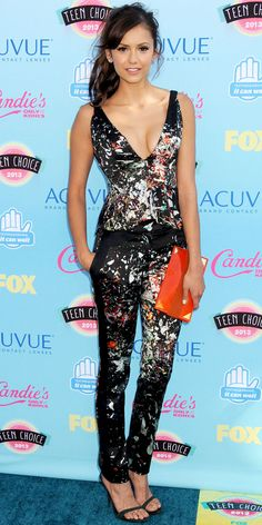 NINA DOBREV At the Teen Choice Awards, Nina Dobrev elected for paint-splattered print J. Mendel separates: A plunging peplum top and matching tailored pants. Diamond Martin Katz earrings, a bright orange Devi Kroell clutch and dark Dolce & Gabbana sandals completed her look.