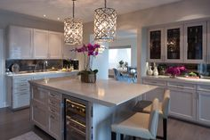 Contemporary gray kitchen features a pair of Ironies Asilah Pendants illuminating a gray kitchen island fitted with a wine cooler topped with a gray quartz countertop and lined with light gray leather barstools with nailhead trim.