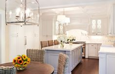 The U-shaped kitchen in white has matching wicker stools at the kitchen island and a lovely cream tile backsplash.