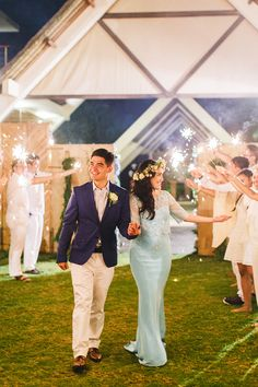 Bride and groom walk in to a surprise guest welcome with sparklers // Yoska and Nariza capped off their week-long celebrations with a bang with a sunset ceremony and dinner reception held at Phalosa Villa, Seminyak, Bali, shot by Haniff Hazim of Wedlocx and planned by Bali Berdua. The couple hosted an intimate, travel-themed destination wedding for their closest friends and family, complete with an encore performance of the flash mob number they performed during their reception in Kuala…