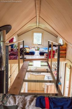 #tumbleweed #tinyhouses #tinyhome #tinyhouseplans Upstairs you'll see something very unusual: two lofts connected by a glass bridge. The childrens' bedroom is on one end with toys and couch beds, and the parents' queen-sized bed is on the other end of the walkway. For more information about what it's like living in a family tiny home, check out their blog.