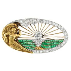 Art Nouveau Gold, Platinum, Diamond and Emerald Brooch   The openwork oval brooch centering one old European-cut diamond with gold wire rays radiating outward, atop a landscape set with square-cut emeralds and a diamond-set sun reflection, edged by old European-cut diamonds, accented by a reclining gold nude female figure wrapped in drapery, circa 1905.