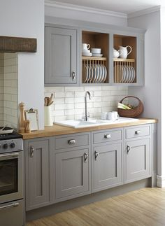 vintage grey kitchen is softened with wooden countertops and a subway tile backsplash makes it more eye-catchy