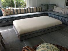 Custom built ottoman using reclaimed lumber with upholstered top and hidden castors