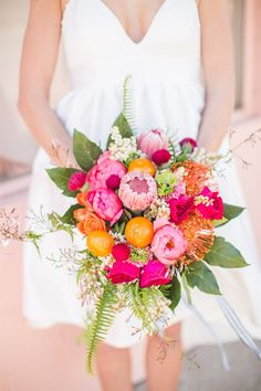 bridal wedding bouquet with protea, clementine fruit, and plenty of pretty flowers - perfect for a spring wedding