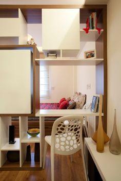 O nicho lateral (à dir.) em marcenaria (Madero) para sala de estar é feito em painéis de MDF branco laqueado. Na estante, um dos espaços pode ser usado como escrivaninha, tanto do lado da sala, quanto do quarto. A cadeira usada aqui é a mesma do espaço para jantar. O projeto de interiores para o apartamento com 32 m² é da designer Adriana Fontana