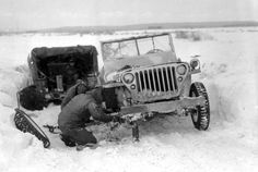 99th Infantry Division GI's work to change a tire and repair their jeep ( a Willy's jeep ) in the snow near Elsenborn, january 27, 1945.