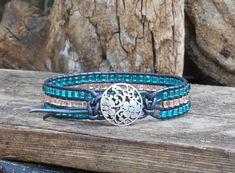 Womens Bracelet Crystal Leather Bracelet Cuff was made using Premium Metallic Gunmetal Leather Cording and stringing Czech Glass Crystals and Glass Seed Beads in stunning shades of Sapphire Blue and Pink-Peach. It closes easily with a metal Silver Flower Button. The total length
