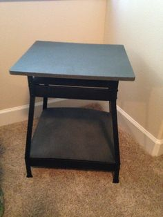 Perfect--place to set a book or lamp, small shelf underneath for other items.  Total cost?  $27 for the tool table, $14 for the 2 cans of rock textured spray paint.