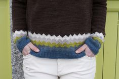 The piece is worked seamlessly from the top down. The back of the boatneck is worked back and forth using German short-rows, and then the yoke is worked in the round with raglan shaping until the yoke is complete. The Sleeves and Body are divided and the Sleeves are placed on hold while the Body is worked to the bottom edge. The Sleeves are worked to the cuff. The Sleeves and Body are worked in Stockinette stitch, with a colorwork chevron band at the bottom edge.