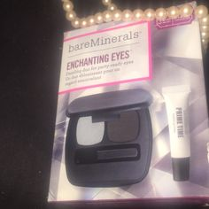 """Bare Minerals Enchanting Eyes Eyeshadow & Primer This charming set of BareMinerals eye makeup includes a full sized Ready 2.0 mirrored eyeshadow palette (with an eyeshadow brush included!) in """"In the Flashback"""" featuring the shades Deja Vu (silver gleam) and Amnesia (charcoal smoke) to create the perfect smoky eye.  It also includes the awesome Prime Time eyeshadow primer.  Everything is neatly wrapped up in tissue paper; all new with tags and never used.  There is a slight tear in the…"""