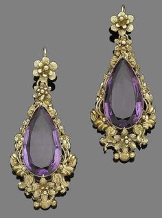 A pair of mid 19th century amethyst pendent earrings Each pear-shaped amethyst within a repoussé and floral surround, suspended from a flowerhead surmount, length 5.8cm: