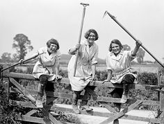 Here, members of the Women's Land Army smile as they hold their tools aloft while climbing over a gate, 1916 ~