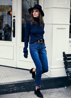 Tricô de gola alta azul marinho, calça jeans azul, cinto com maxi fivela, sapato preto