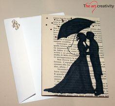 Biglietto di auguri per matrimoniocon shiluette stosi su di una pagina da libro.