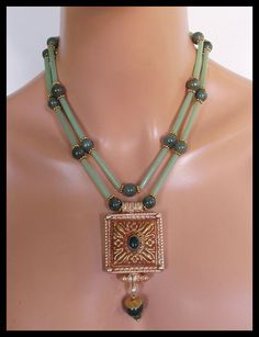 Intricately detailed, handmade brass/copper/silver Tibetan repousse prayer box pendant hangs from necklace made of 2 strands of aventurine tubes and round jade beads accented by brass Bali style spacers. Prayer box has inlay of jade and I have added jade bead topped by handforged