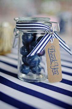 Le petit pot en verre customisé d'un ruban raye bleu marine et blanc et d'une étiquette marque place en papier Kraft. http://mariageetreception.fr/88-marin