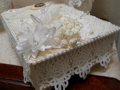 This handmade Shabby Chic Box,Table top box, jewelry box, keepsake box, wedding box, baby shower box was sanded down, primed and painted a creamy ivory. I then covered it with numerous shabby laces, doilies, fabric flowers, pearls, cameo, Satin Flowers, - and can be used everywhere. It is 12 x 8 x 4 inches in measurements and has little wooden feet to stand on. Thank you for looking, Overcharged shipping will always be reimbursed.