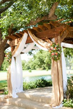 Burlap draping with country pink and green flowers over a wooden pergola.
