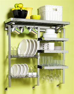 Pegrail Complete Kitchen Rack. Wall-mounted rack holds dishes, glassware, coffee mugs, etc. Shelf space allows storage for a silverware bucket and even some cookware. It's a bit expensive, but a DIYer could probably create a similar design for a lot less. Check it out here: http://www.kitchen-furniture-gallery.com/IVG2/Y/ProductID-304381-.htm