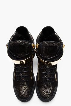 GIUSEPPE ZANOTTI - Black and Gold Printed Python London Sneakers High top leather sneakers in black and metallic gold. Snakeskin pattern printed throughout. Round toe. Gold-tone hardware. Tonal lace up closure. Zip closure at eyerow. Black suede logo patch at bellows tongue. Signature metal bar detail at midrow with Velcro closure. Extended collar with zip closure at heel. Black patent leather panel at heel collar. Textured black rubber sole. Tone on tone stitching. Made in Italy. $935 CAD